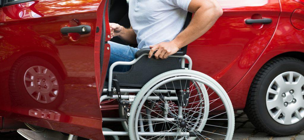 Rollstuhlfahrer an der Fahrertür des Autos