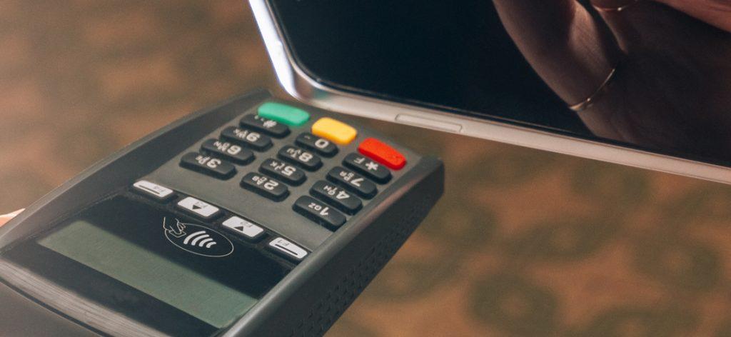 Handy wird an elektronisches Kartenlesegerät gehalten