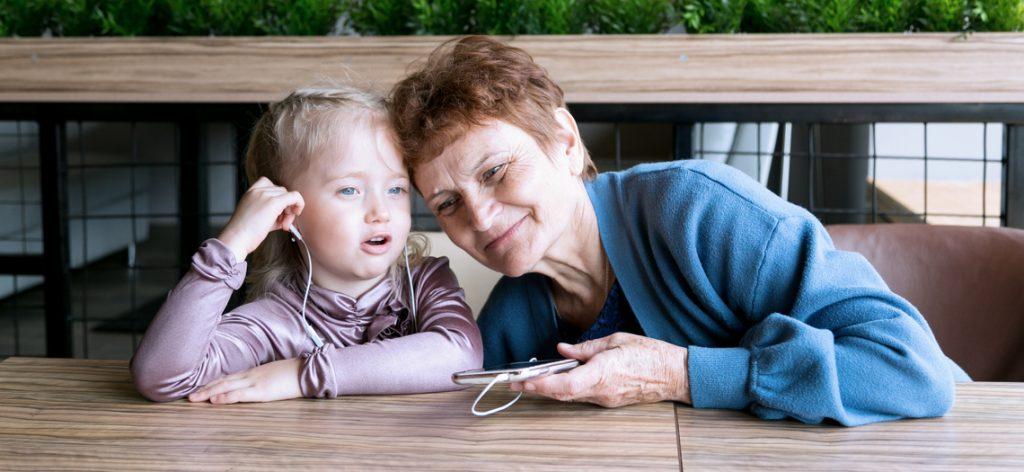 Alte Frau teilt sich mit Kind einen Kopfhörer