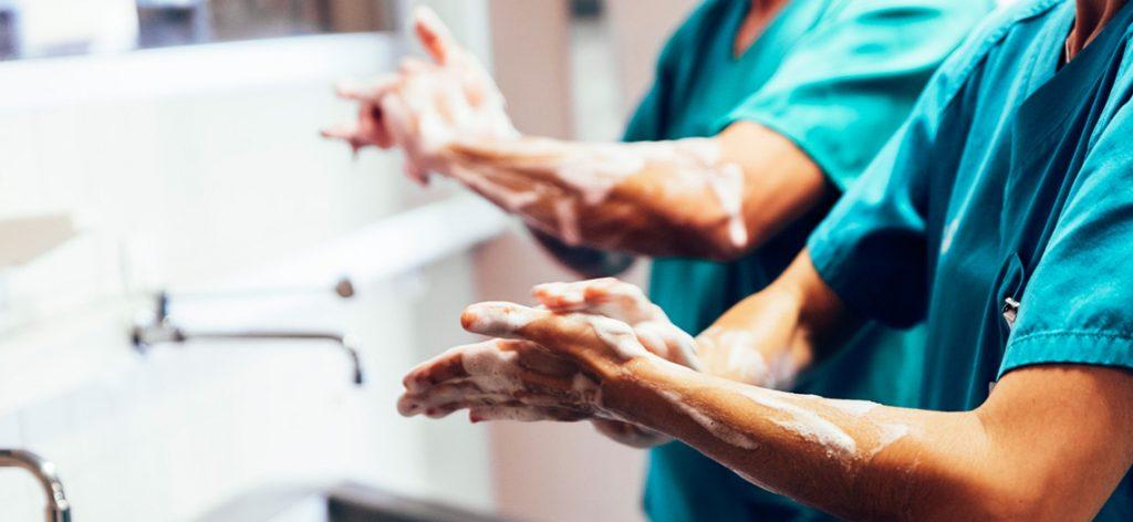 zwei Personen desinfizieren sich die Hände
