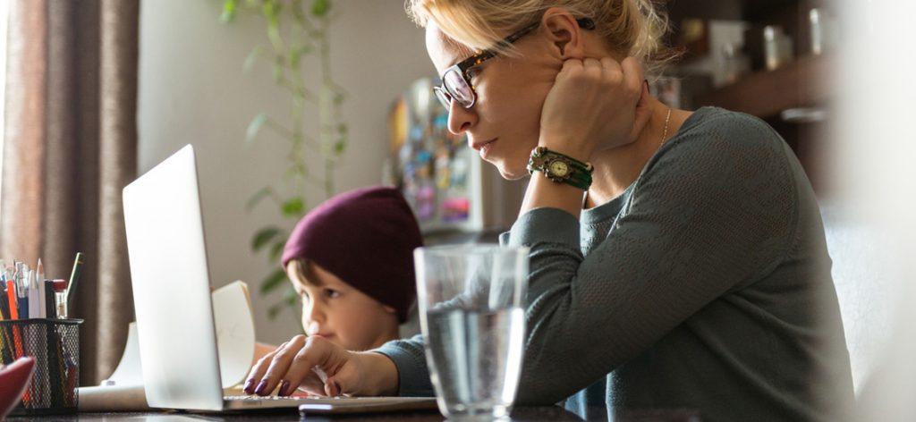 Frau Sitzt vor dem Laptop, neben ihr ein Kind