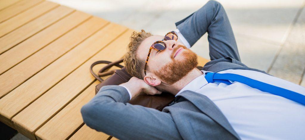 Mann mit Sonnenbrille liegt entspannt auf einem Steg