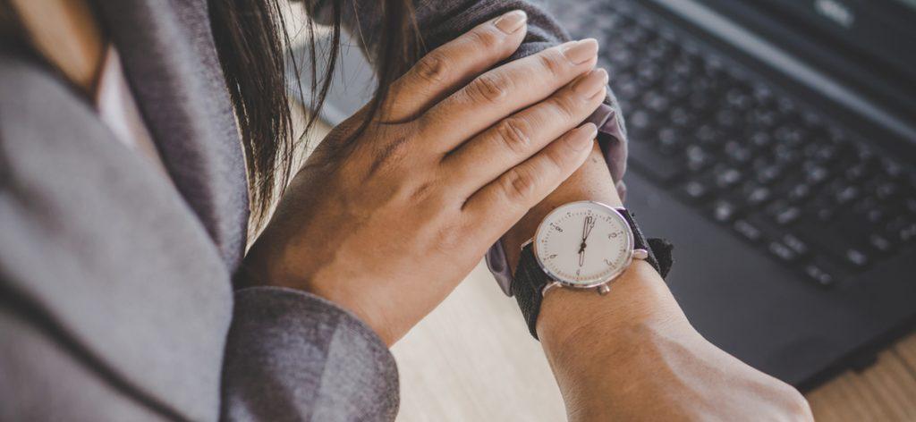 Nahaufnahme von Frau, die auf die Uhr schaut