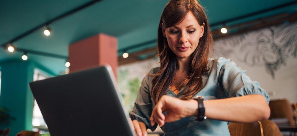 Eine Frau sitzt am Laptop und schaut auf die Armbanduhr