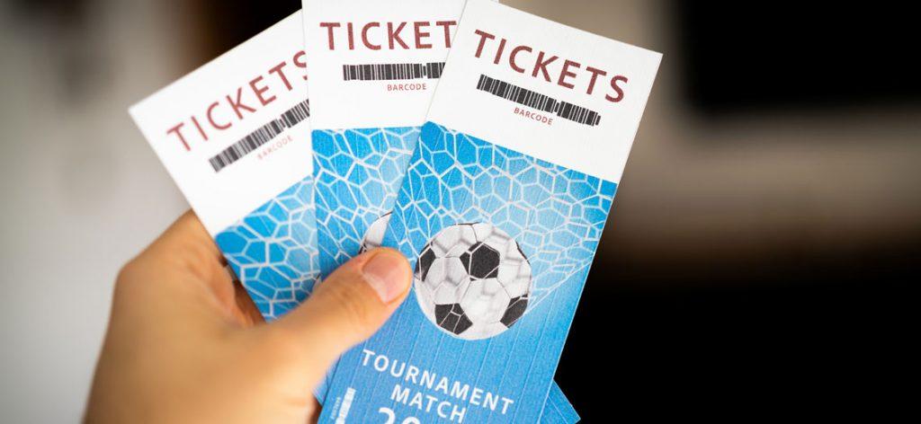 Nahaufnahme einer Hand, die zwei Karten für ein Fußballspiel hält