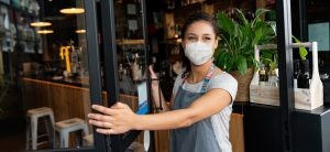 Junge Frau mit Mund-Nasen-Schutz öffnet die Tür eines Cafés