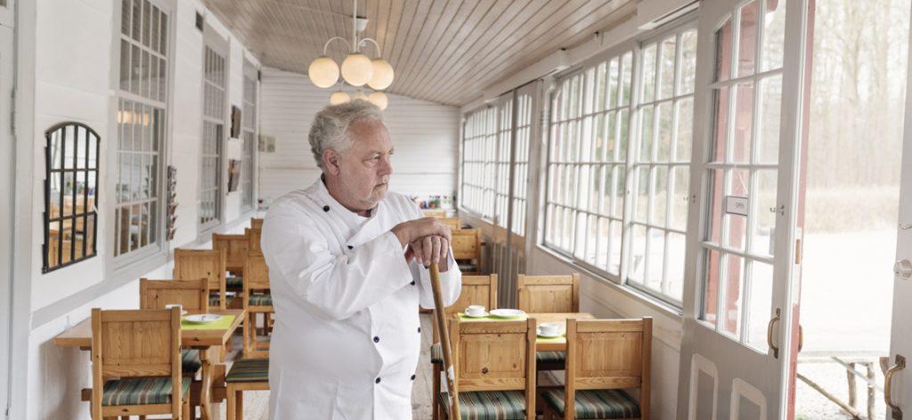 Mann in Kochjacke, steht in leerem Restaurant
