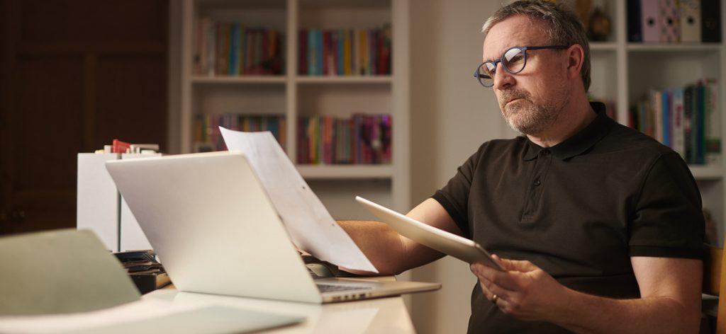 Mann schaut sich besorgt Unterlagen vor dem Laptop an