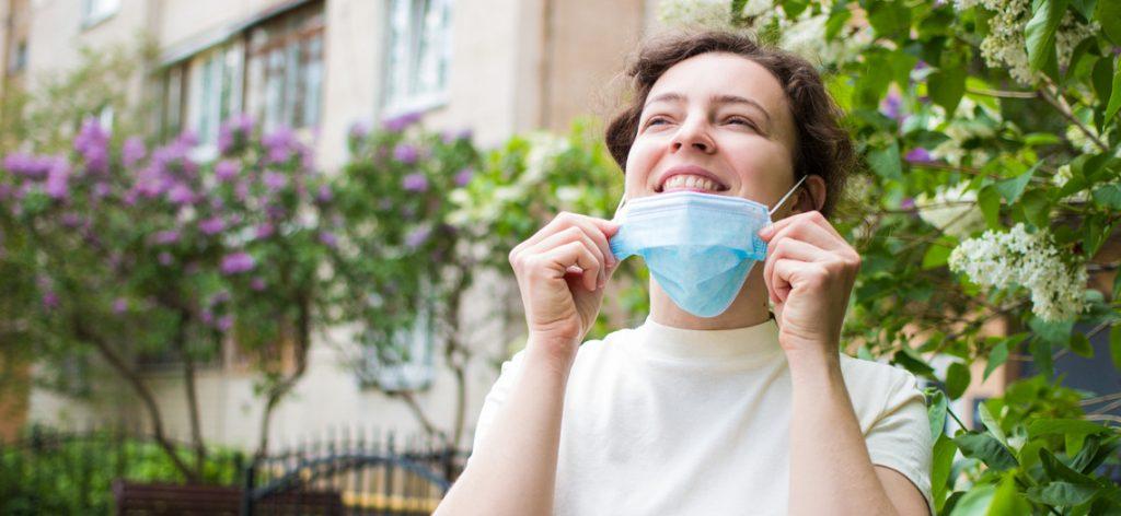 Frau zieht sich glücklich lächelnd den Mund-Nasenschutz herunter