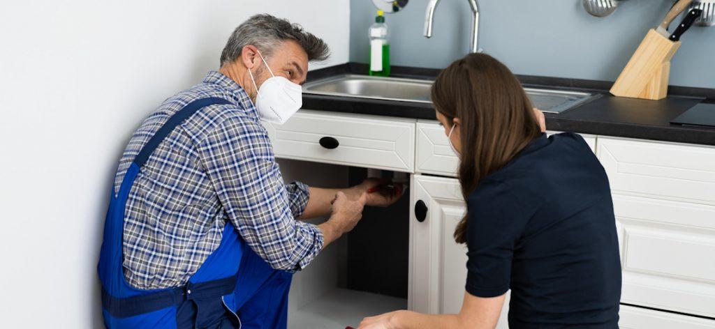 Handwerker repariert Abfluss in der Küche