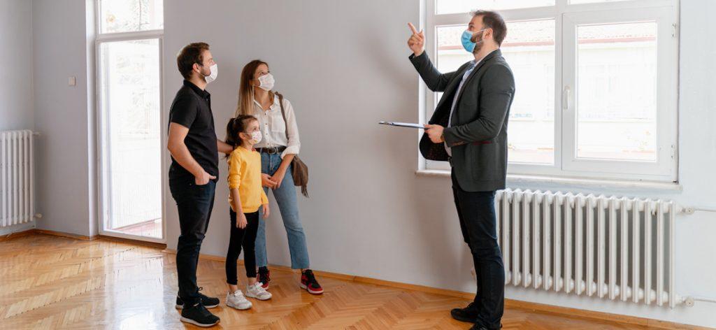 Makler zeigt glücklicher Familie eine Wohnung
