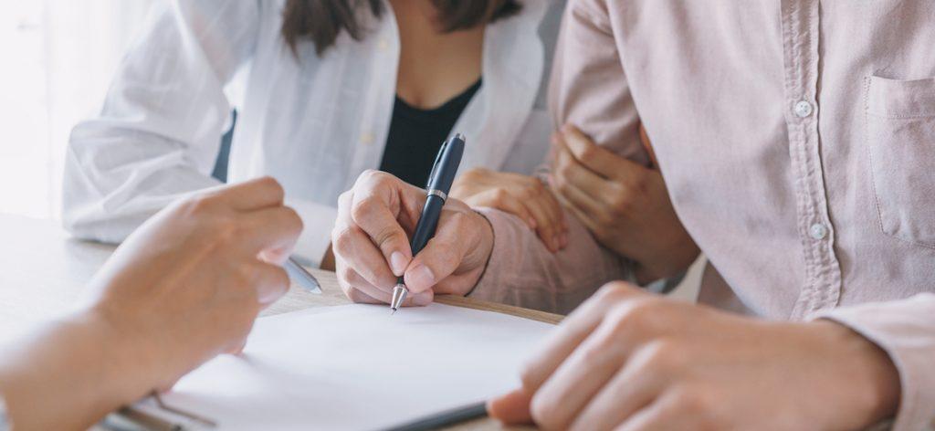 Paar tätigt Unterschrift auf Vertrag