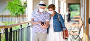 Älteres Paar schaut auf ihr Handy und tragen Masken
