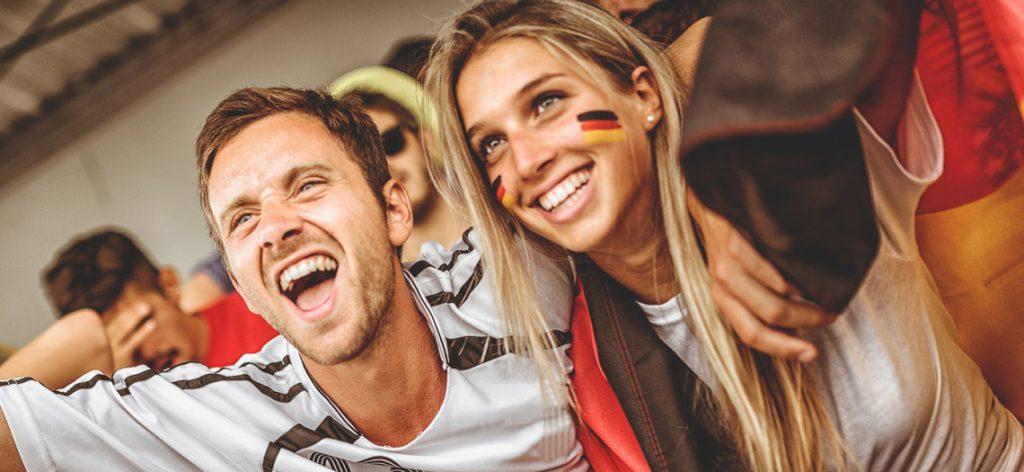Junges Paar im Fußballfieber feuert die Deutsche Mannschaft an