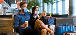 Junges Paar wartet am Flughafen und trägt dabei einen Mund-Nasenschutz.
