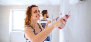 Glückliche junge Frau streicht Zimmerwand