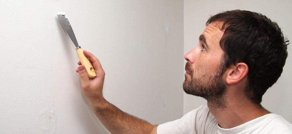 Mann streicht skeptisch eine Wand