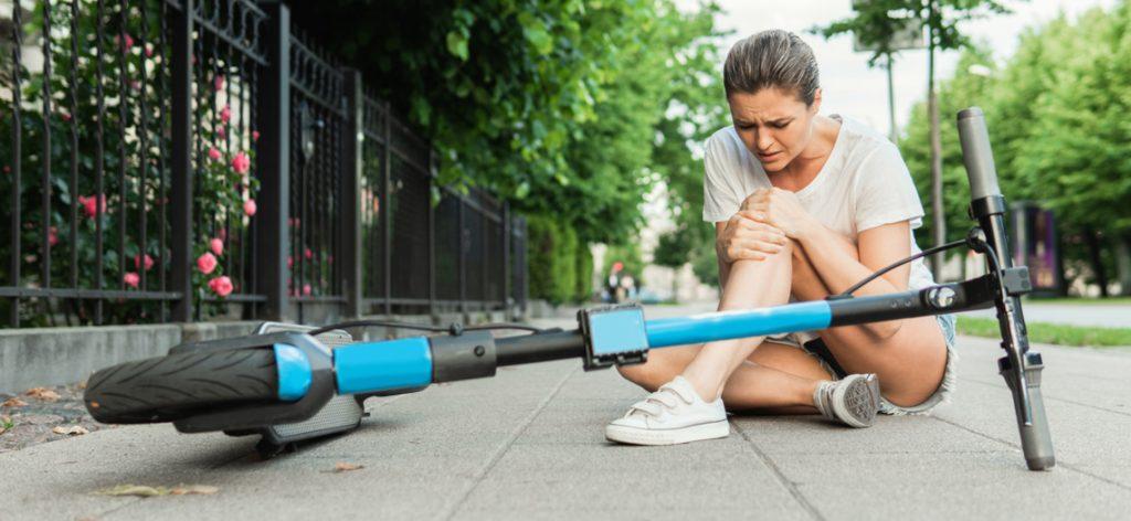 Junge Frau hält sich ihr Knie, nachdem sie mit dem E-Scooter gestürzt ist