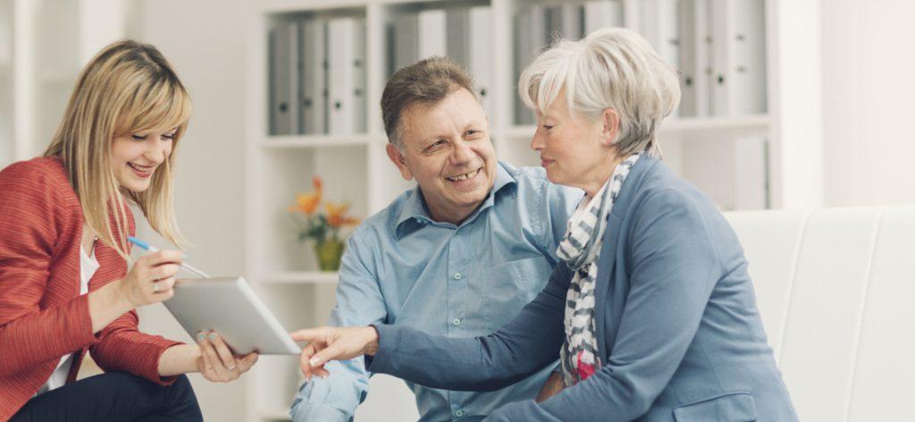 Junge Frau zeigt glücklichem älteren Paar etwas auf dem IPad