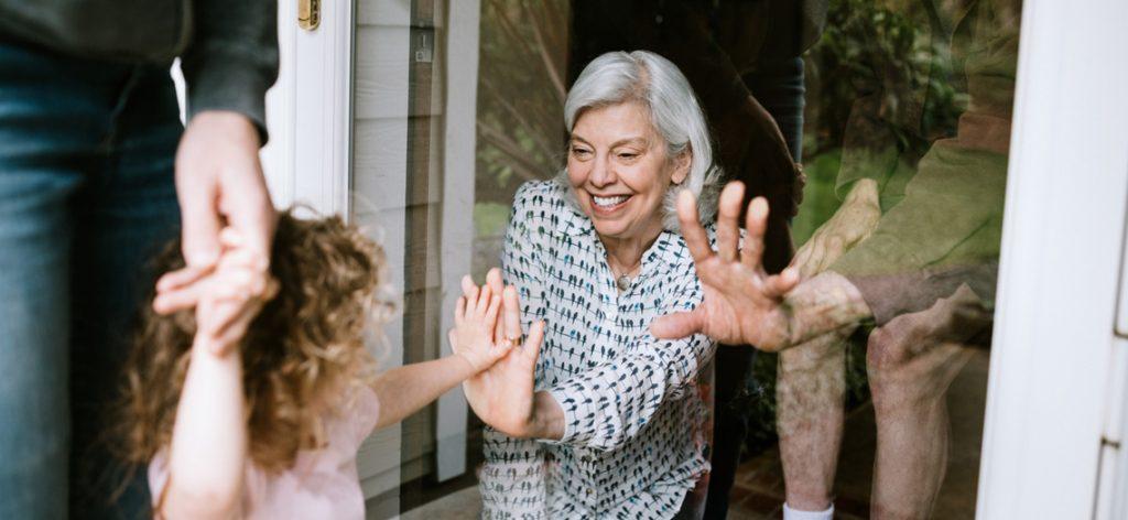 Oma sieht ihre Enkelin durch Fensterscheibe und freut sich