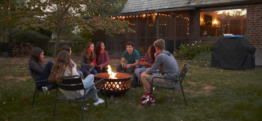 Freunde unterhalten sich, während sie um eine Feuerschale sitzen