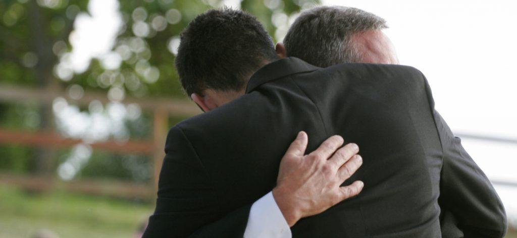 Zwei Männer umarmen sich tröstend.