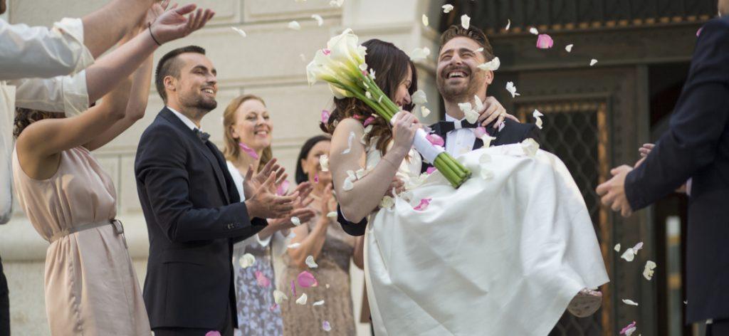 Braut und Bräutigam verlassen das Standesamt und werden von den Gästen mit Blütenblättern beworfen.