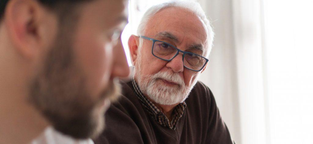 Besorgter älterer Mann spricht mit seinem Sohn.