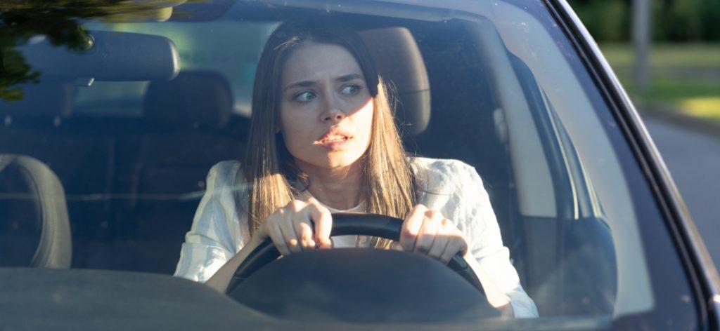 Junge Frau fährt Auto und schaut erschrocken.