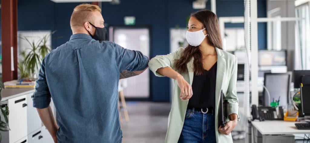 Zwei Arbeitskollegen mit Masken begrüßen sich mit dem Ellbogen.