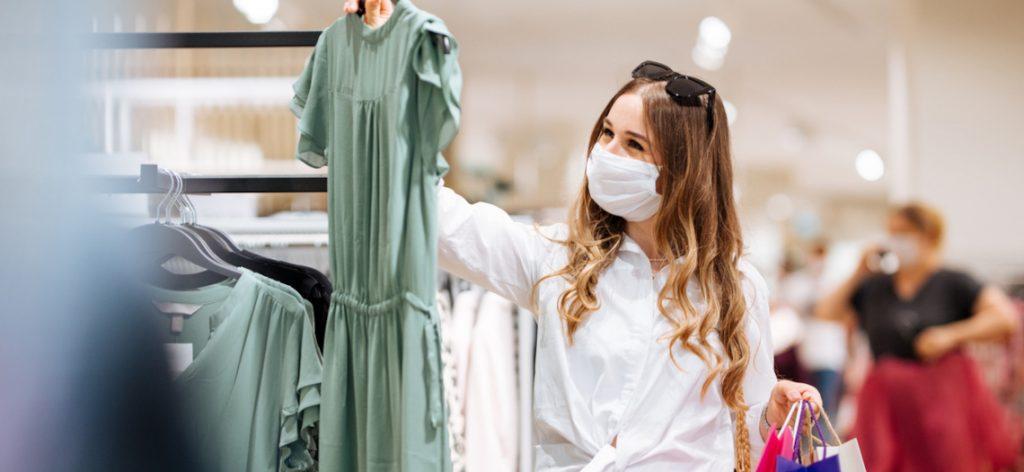 Frau trägt Maske und kauft Kleidung ein.
